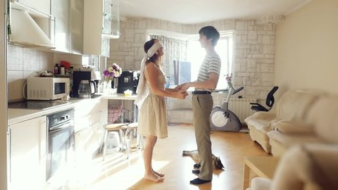 husband leads his wife with a blindfold on her eyes in their new home this is surprise and young couple embrace in their new flat in slowmotion while cat liyes on the floor. 1920x1080