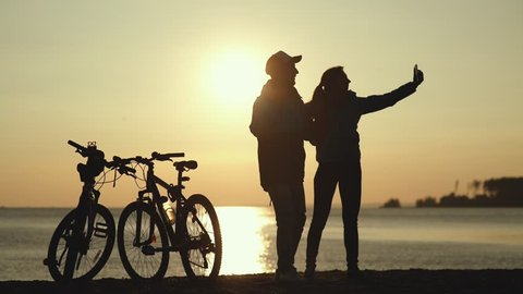 Silhouettes of two cyclists at sunset. The pair finished the bike ride on the river and do selfi on a beautiful background. Couple in love. Unusual date. hotograph on a mobile phone