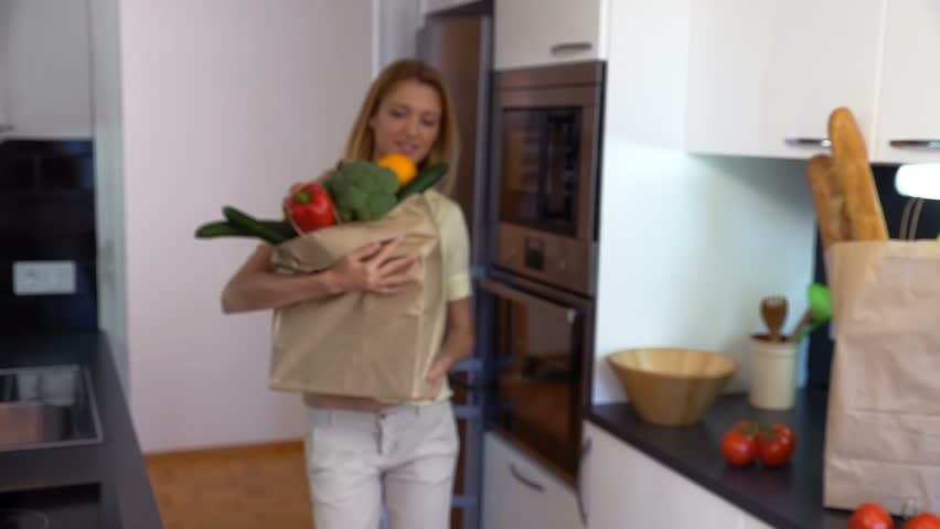 Happy young woman brings to the kitchen a large paper bag of groceries and smiling at the camera. Slow motion.