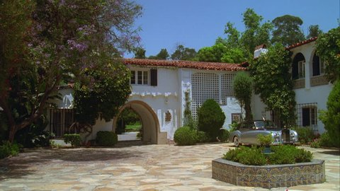 day from inside courtyard POV an upscale large Spanish style two story house, stucco house, arched driveway entrance, early 1990s Rolls Royce parked right, convertible sports car Jaguar enters