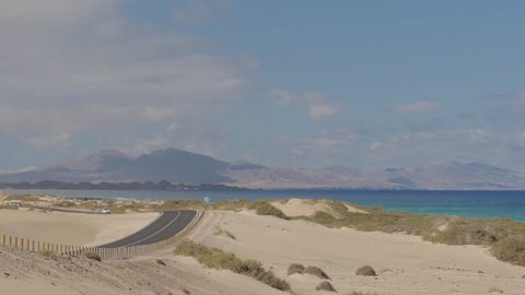 Road through the sand dunes near Corralejo, Fuerteventura, Canary Islands, with the island of Lanzarote in the background.