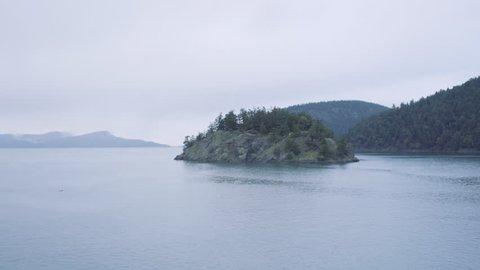 Sailing past a tiny island in the San Juan Islands, Washington, USA.