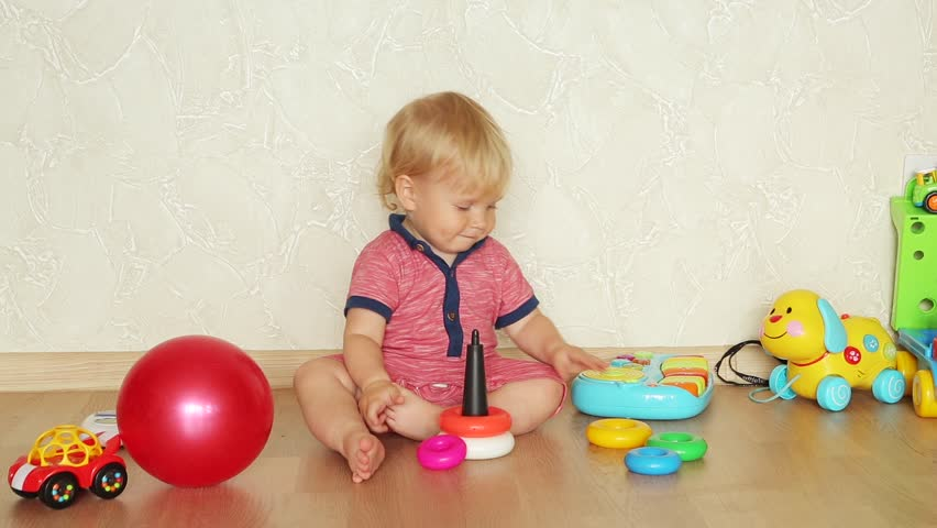 One year-old child playing with educational cup toys at home. Little blonde baby boy with blue eyes is playing with pyramid toy on the floor. Little kid have fun indoors | Shutterstock HD Video #20339032