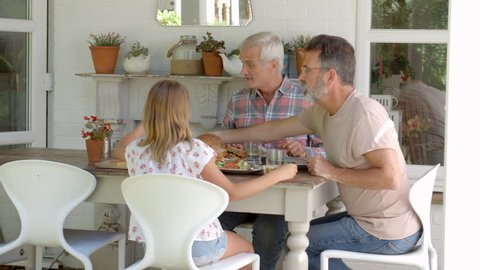Same Sex Family At Home Eating Meal On Outdoor Verandah