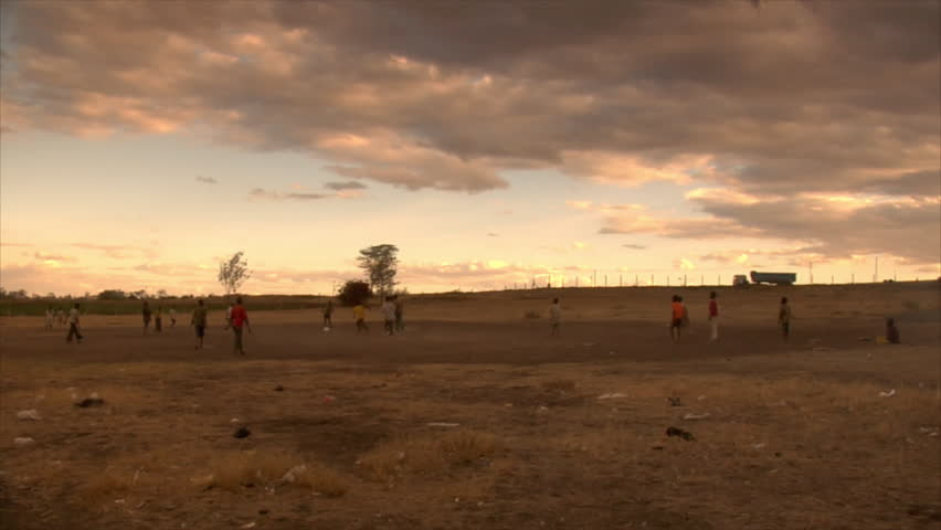 Unidentified boys play soccer in the street in the evening circa 2006 in Kenya.