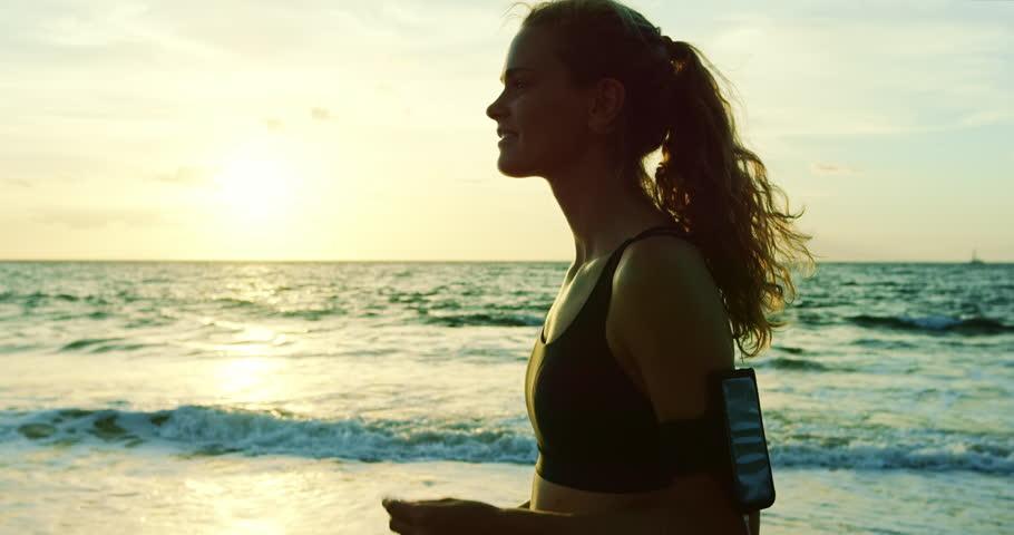 Athletic young woman enjoying sunset run on the beach | Shutterstock HD Video #20348572