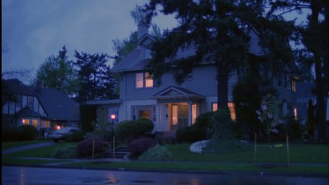 Late day stormy day dusk Nice large light gray 2 story house traditional eastern house dormers Lights Wet street light rain after storm Rake right