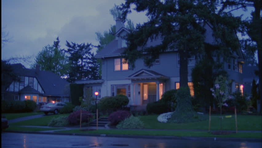 Late day stormy day dusk wider Nice large light gray 2 story house traditional eastern house dormers Lights Wet street light rain after storm Rake right, blue truck then red truck camper shell