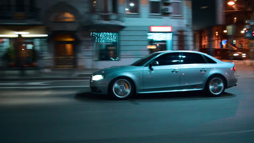 Side shot of a blue car driving in a city street at night | Shutterstock HD Video #20363392