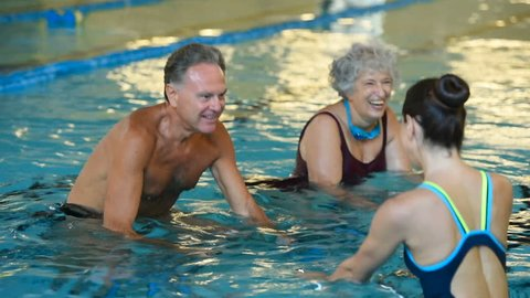 Happy smiling mature man and old woman cycling on a swimming bike. Happy and healthy senior people doing water aerobics on exercise bikes in a swimming pool. Fitness class training in swimming pool.