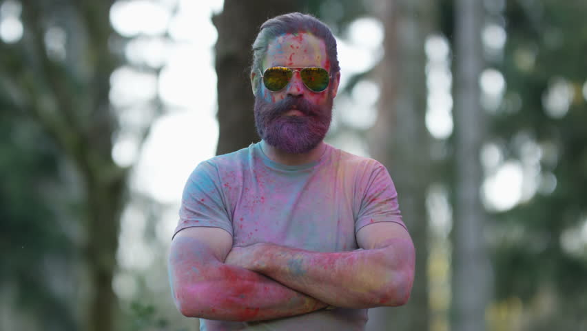 4K Portrait of serious hipster guy standing still while being covered in coloured powder at festival. Shot on RED Epic. | Shutterstock HD Video #20370652