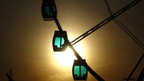 Skywheel cabins against bright evening sun. Ferris wheel gondolas silhouette view, sunlight shine through cyan glass. Empty pods hang on steel frame, slowly rotate against dark sky and bright sunshine