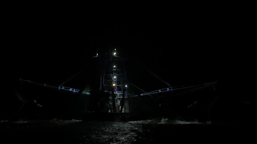Shrimping trawler fishing at night with nets in the water.