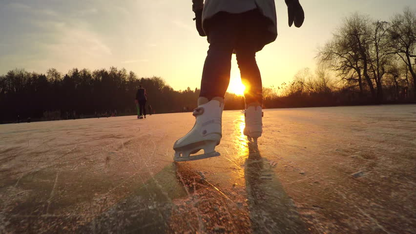 CLOSE UP, LOW ANGLE VIEW: Happy woman iceskating fast on frozen pond in local park at golden sunset on magical Christmas evening. People on ice skates enjoying winter activities in nature, having fun