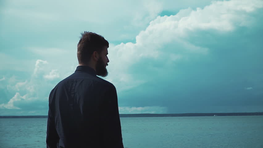 Young stylish man with a beard smokes an electronic cigarette in the background of the sea and clouds epic. Modern fashion vaping