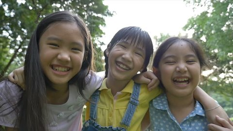 Slow motion shot : Group of little happy Asian girls playing together in the park
