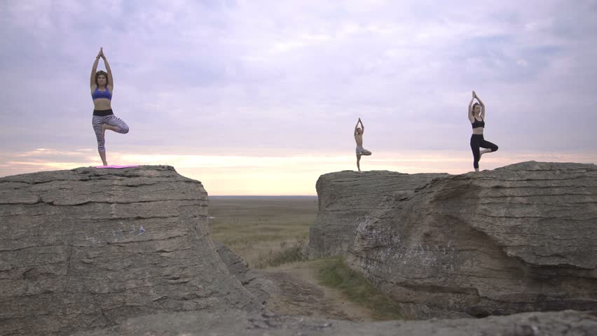 Two girls and one boy doing yoga at dawn | Shutterstock HD Video #20488834