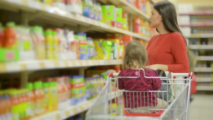 Mother and child walks along wholesale shelves and taking goods in shop trolley, beautiful young wife shopping in a supermarket | Shutterstock HD Video #20495272