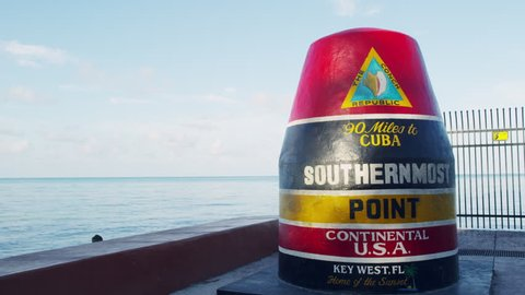 A beautiful cinematic tilting/panning shot of the Key West Southernmost Point landmark in Key West, Florida at sunrise.