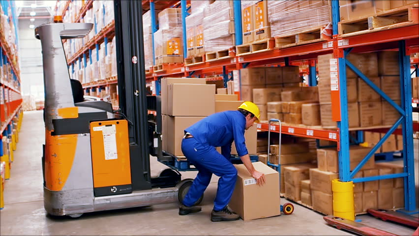 Warehouse worker looking at packages in warehouse 4k stock footage male worker loading cardboard box on forklift in warehouse hd stock video clip sciox Choice Image