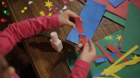 little girl glue handicrafts made of colored paper