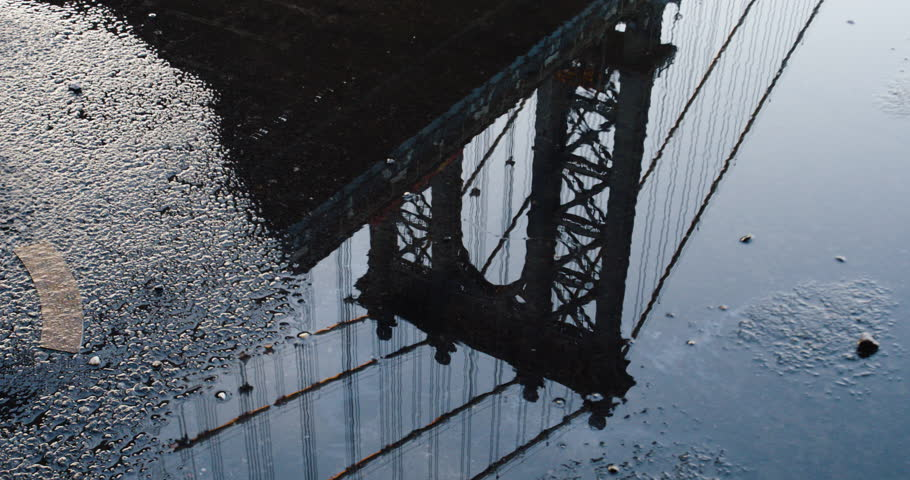 A closeup shot of a puddle in the street as it casts a reflection of New York City's Manhattan Bridge. (Jul 16 - New York City)
