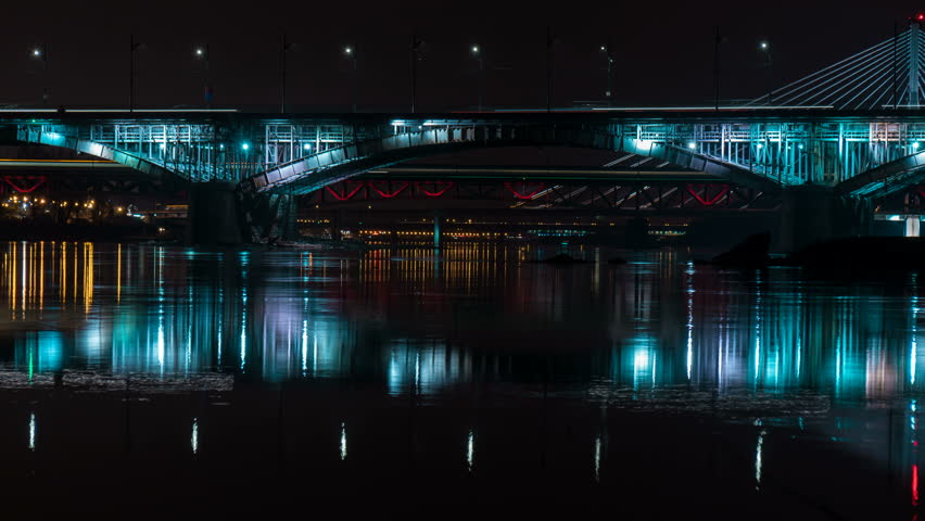 Timelapse of busy bridges in Warsaw with Vistula river at night.