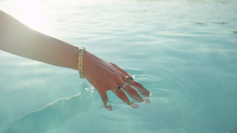 SLOW MOTION CLOSE UP: Unrecognizable young female caressing water with soft hands and sliding with fingers on its surface on sunny summer day. Happy girl on relaxing vacations in luxury tourist resort