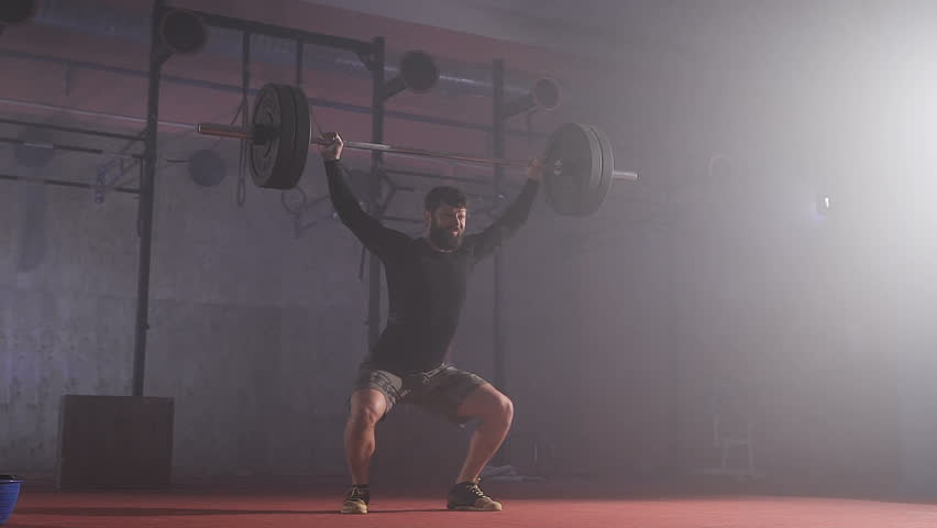 Strong man doing barbell snatch exercise at the gym in slow motion. | Shutterstock HD Video #20584402