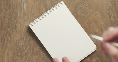female teen writes to do list on blank notepad