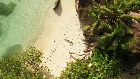 Aerial motion view of Seychelles tropical beach Anse Source D Argent at La Digue island with young woman sunbathing