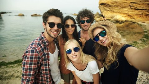 Funny friends in sunglasses taking selfies.