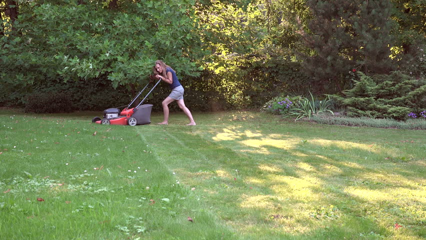 Barefoot blonde woman cut meadow with lawn mower in green garden. video clip. | Shutterstock HD Video #20627962