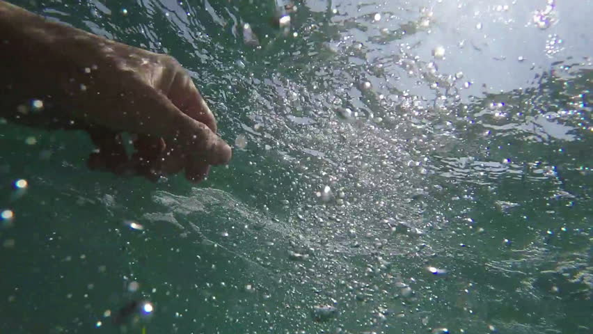 Man drowning in the sea, hand asking for help sticking out of cold water with air bubbles, pov shot