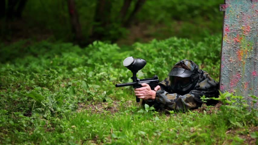 Boy paintball player lies with gun in ambush on grass near metal fence