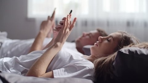 Handheld shot with rack focus of young man and woman lying in bed in morning and looking at their mobile phones