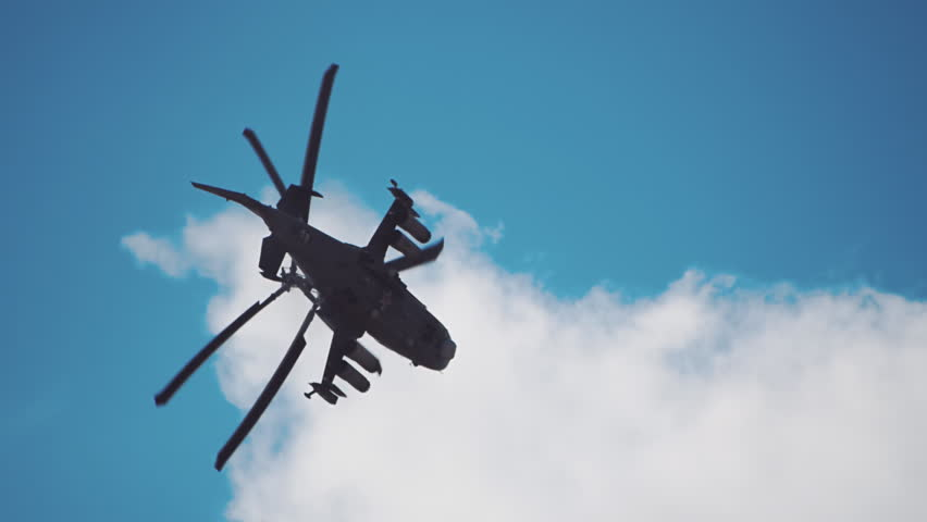 "Reconnaissance and attack helicopter of the new generation Ka-52 ""Alligator"" performs aerobatics on a background of blue sky and clouds. Includes audio. Contains audio 