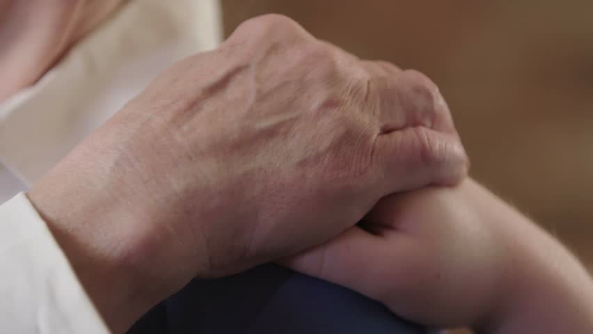 A woman puts a comforting hand on an older elderly woman's shoulder. The older woman puts a hand on the other hand. Shot in 4K UHD.