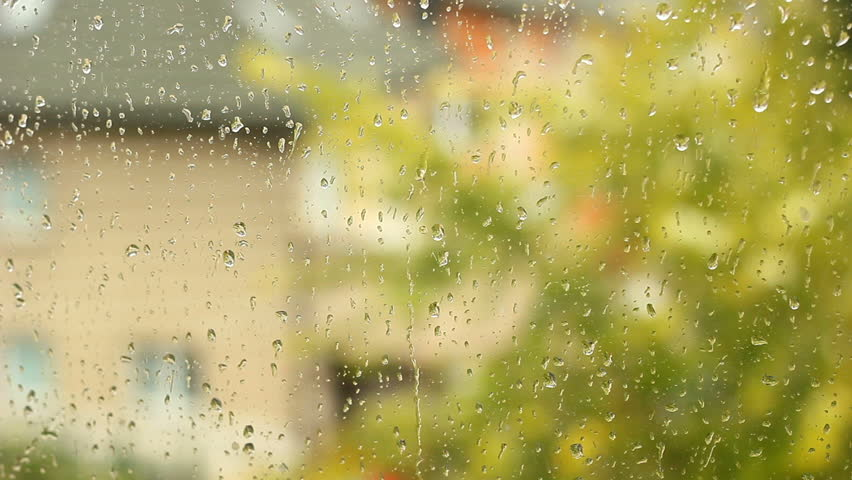 Rainy day in fall. The rain drops on household windows. Focus on rain drops running down the window.