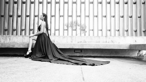 Gorgeous fashion woman with dark hair in elegant black dress looking into the camera while sitting and posing on the bench in modern tropical garden - black and white video in slow motion