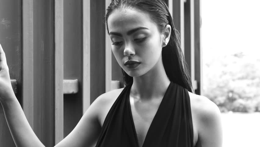 Closeup face portrait of gorgeous fashion woman with dark hair in elegant black dress looking into the camera while walking along modern wall in tropical garden - black and white video in slow motion
