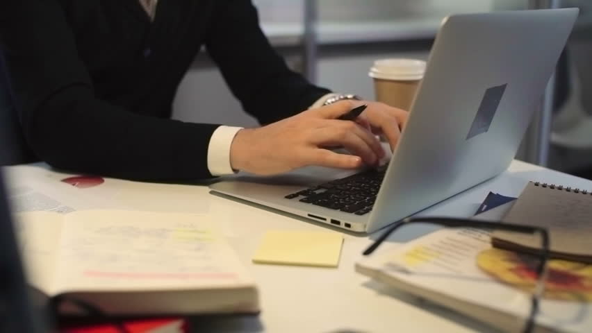 PAN with low section of male hands typing on laptop and then writing something down on post-it note | Shutterstock HD Video #20763022