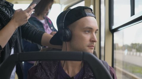 Young man in cap sitting in bus looking out window and listening to music in headphones