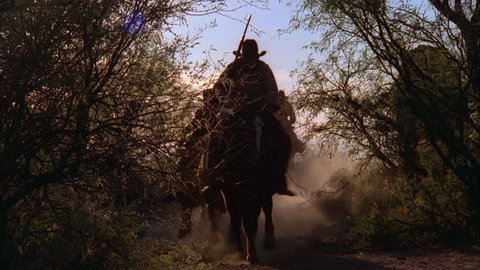day desert rural brush then see group cowboys horseback riders ing rifles fast toward camera path through bushes western TV playback, channel surfing