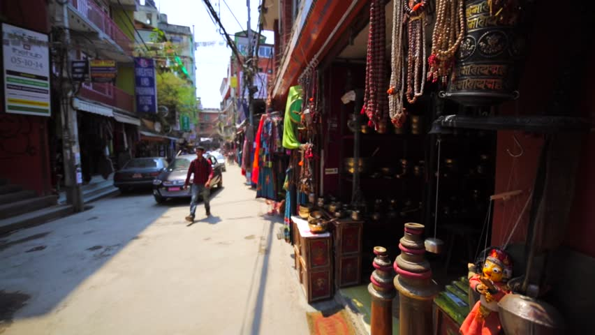 KATHMANDU, NEPAL - APRIL 8, 2016: Walking along the street with selling stands with clothes, textile, souvenirs and driving cars and walking people. Thamel district, the most popular among tourists