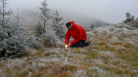 Fire. Hiker kindles a fire using flint, frosty morning in mountains. The concept of survival.Starting fire with firesteel. Fire. Fireplace. Fire wild. Bonfire. Campfire. Kindle fire. Kindling fire.
