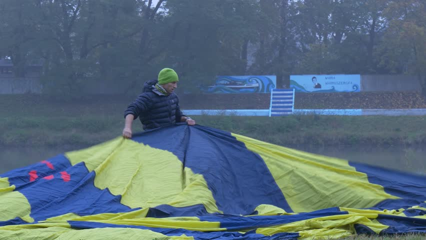 Opole/poland - Oct 22 2016: a Man in a Blue Jacket and Green Hat Lays Balloon on a Green Grass Field. he Spreads the Cloth Yellow Blue. in the Background the River and Trees. Event: Ballooning on | Shutterstock HD Video #20812822