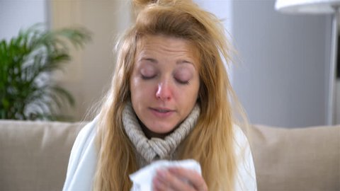 A woman with fever and runny nose uses nasal spray and sneezes loudly.