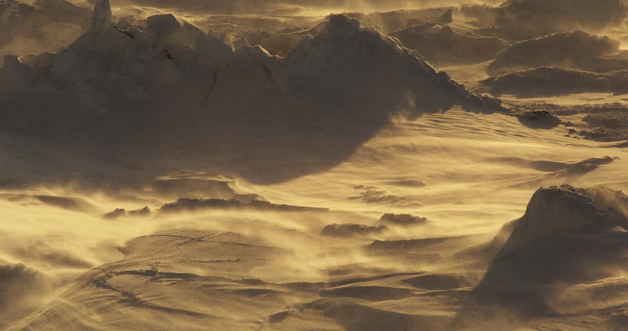 Close on snow blowing over drifts in arctic storm and golden light
