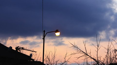 Dusk to night in the suburbs in village. Streetlight stays on at moving clouds with dramatic red sky in timelapse